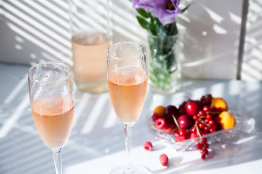 glasses of pink wine on the table next to a bottle and fruit