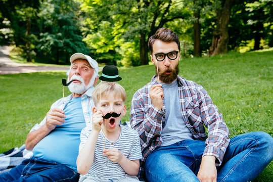 Happy funny family son and dad, granddad with fake mustache, hat, eyeglasses on holiday outdoor in park. Good day, happiness, friendship, stroll, holiday concept.
