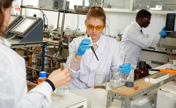 Woman lab technicians in glasses working with reagents and test tubes
