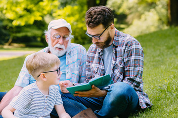 happy family of three generation - father, grandfather and cute blond son sitting on grass at park...