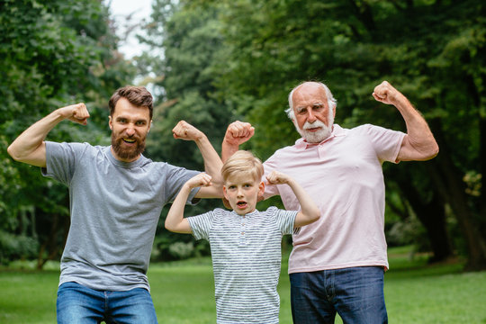 Portrait og happy family - grandpa, father and his son smiling and showing their muscles outdoor in park on background. Three different generation concept.