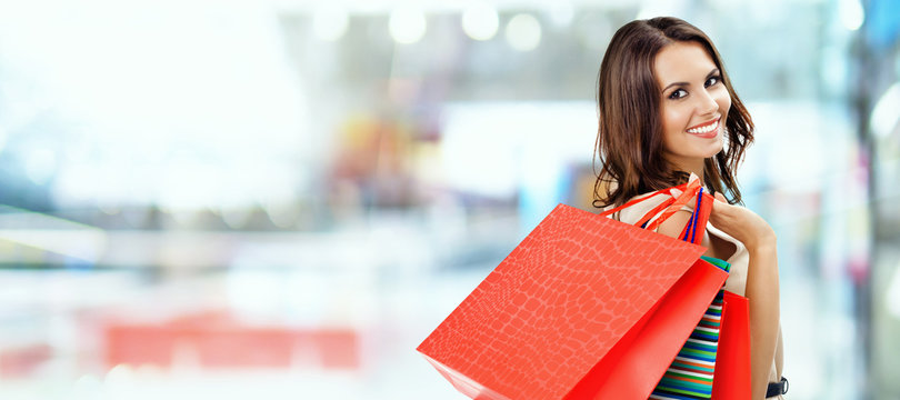 Picture of happy beautiful girl with color shopping bags, at mall