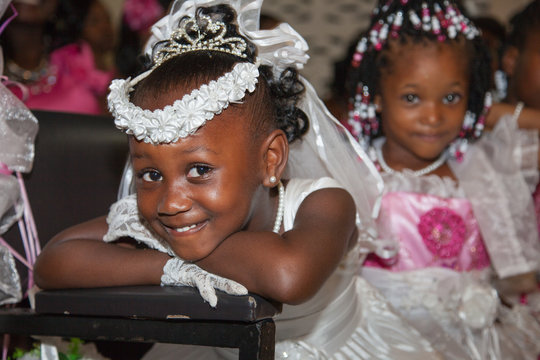 Funny African-American girls in wedding dresses at the wedding. Very cute kids in the Wedding Ceremony. Selective focus.