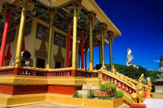 View on golden pillars, drum and white buddha statue against blue sky at Buddhist temple - Wat Ek Phnom, near Battambang, Cambodia