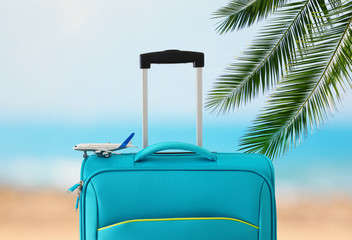 Wall Mural - holidays. travel concept. blue suitcase and airplane toy infront of tropical background