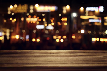 background of wooden table in front of abstract blurred restaurant lights Fotomurales