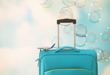 Wall Mural - holidays. travel concept. blue suitcase and airplane toy infront of sky with soap bubbles background