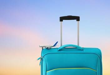 Wall Mural - holidays. travel concept. blue suitcase and airplane toy infront of sunset bokeh background