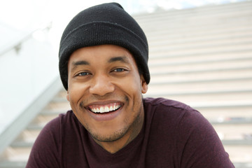 Close up cool young black man with beanie smiling