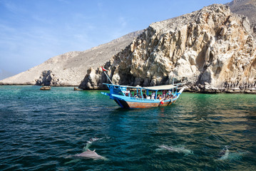 Khasab, Oman: Tourist seeing dolphins from boat.