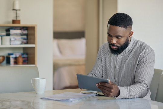 African American man doing his online banking with a tablet
