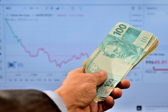 Dinheiro na mão de homem comprando ações no mercado de valores
