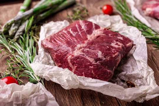 Raw hanging tender beef BBQ steak on wooden Board with rosemary and asparagus and tomatoes. wooden background, top view