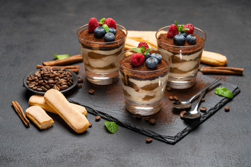 Classic tiramisu dessert with blueberries and raspberries in a glass and savoiardi cookies on stone serving board on dark concrete background