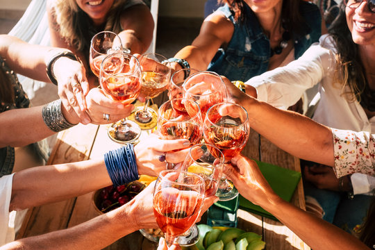 Happy and cheerful group of people females young friends together cheering and toasting celebrating with red wine - happiness and friendship concept during party event for happy women