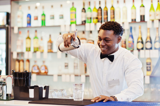 African american bartender at bar with shaker. Alcoholic beverage preparation.