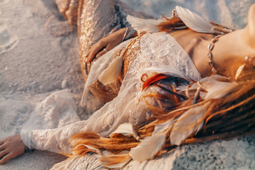close up of beautiful young woman in elegant dress lying on sand on the beach at sunset time