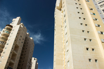 common modern concrete living buildings in city street area photography foreshortening from below on saturated and vivid blue sky background