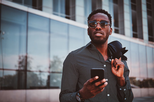 Portrait of pensive modern afro man with sunglasses and mobile phone over glass building background.