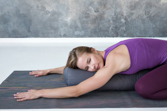 Beautiful slim woman doing yoga exercise for spine and rest lying in Child Pose, Balasana Posture after practice. Full length view