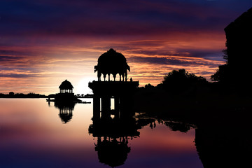 Wall Mural - Silhouettes of gazebos while sunset at Gadisar Lake, Jaisalmer, Rajasthan, India