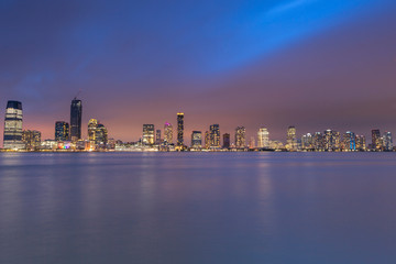 View on Jersey City skyscrapers at sunset from Hudson river with long exposure