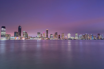 View on Jersey city skyscrapers at night from Hudson river with long exposure