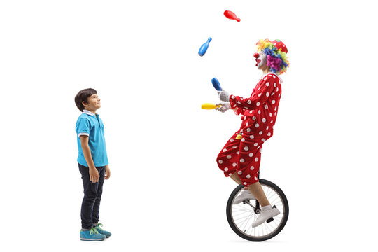 Boy watching a clown juggling and riding a unicycle