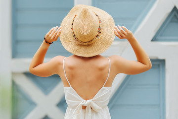 Wall Mural - Young woman in light summer clothes and straw hat in blue background. Summer Vacation concept