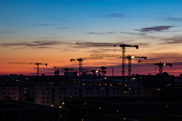 Construction cranes in the sunset in front of housing near the Munich trade fair area in Bavaria, Germany
