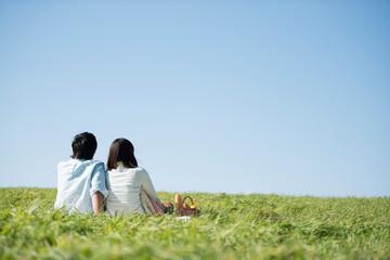 草原でピクニックをするカップルの後ろ姿