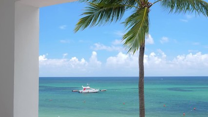 Fototapete - View from balcony resort on caribbean beach with coconut palm trees and boat floating in turquoise sea. Travel destinations. Summer vacation