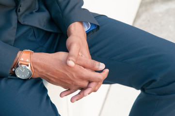 Closeup of businessman clasped hands. Dark skinned man in office suit sitting outside and keeping fingers interlocked. Body language concept