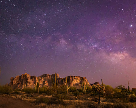 The iconic Superstition Mountains east of Phoenix, Arizona glow under the desert night sky and the epic Milky Way Our world under our universe in star filled dark skies is natural beauty