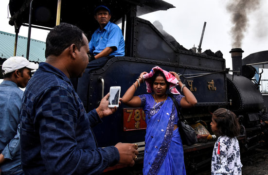 Passengers stand next to a Darjeeling Himalayan Railway steam train, which runs on a 2 foot gauge railway and is a UNESCO World Heritage Site, as it halts briefly at Batasia Loop in Darjeeling