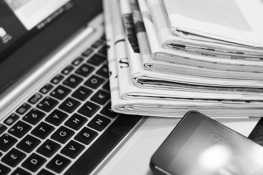 News. Newspapers, Laptop and Smartphone - Sources of Information. Finance Magazines and Journals Stacked in Pile on Keyboard of Computer. Business Concept
