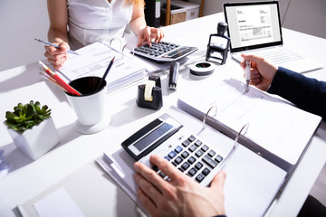 Businesspeople Calculating Invoice With Calculator