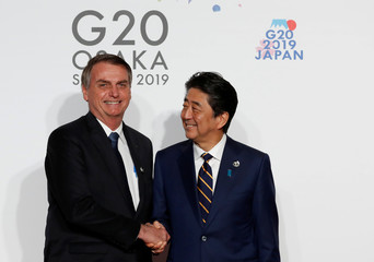 Brazilian President Jair Bolsonaro is welcomed by Japanese Prime Minister Shinzo Abe upon his arrival for a welcome and family photo session at G20 leaders summit in Osaka