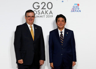 Mexico's Foreign Minister Marcelo Ebrard is welcomed by Japanese Prime Minister Shinzo Abe upon his arrival for a welcome and family photo session at G20 leaders summit in Osaka