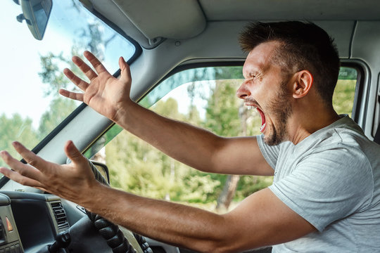 Aggressive Man, the driver of the car is outraged at the wheel during the trip. Emergency, accident, violation of rights, dispute, bad driver