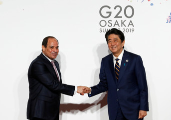 Egyptian President Abdel Fattah el-Sisi is welcomed by Japanese Prime Minister Shinzo Abe upon his arrival for a welcome and family photo session at G20 leaders summit in Osaka