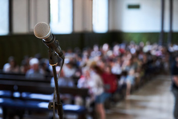 Microphone and abstract blurred conference hall or seminar room background