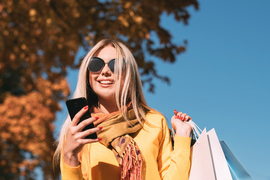 Modern woman leisure. Happy lady walking with shopping bags, using smartphone for chatting. Blur autumn trees and sky background.