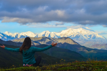 Girl watching a morning view of Mount Denali - mt Mckinley peak during golden hour from Stony Dome overlook. Denali National Park
