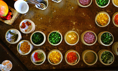 Mise en place of little dishes with ingredients for making tropical ceviche
