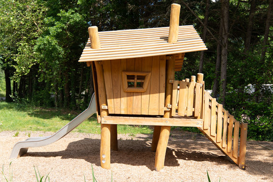 little wooden playhouse in a public park with stairs and windows
