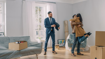 Real Estate Agent Shows Bright New Apartment to a Young Couple. Successful Young Couple Becoming Homeowners. Girl Jumps Into His Boyfriend's Arms Hug. Spacious Bright Home with Big Windows.