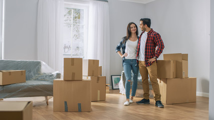 Happy Young Couple Moving Into New Apartment, Carrying Cardboard Boxes with Stuff and Poses on Camera. Young Boyfriend and Girlfriend Start Living Together, Unpacking Stuff.