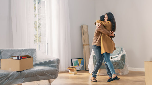 Happy and Excited Young Couple Look Around In Wonder at their Newly Purchased / Rented Apartment. Beautiful People Happily Embracing. Big Bright Modern Home with Cardboard Boxes Ready to Unpack.