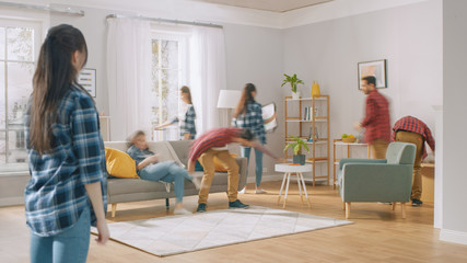 Time-Lapse Silhouettes or Blurred Happy Young Couple Moves into New Apartment, Arranges Furniture, Hanging Paintings, Resting on a Couch. Bright Modern House with Big Windows and Stylish Furniture. Fotobehang
